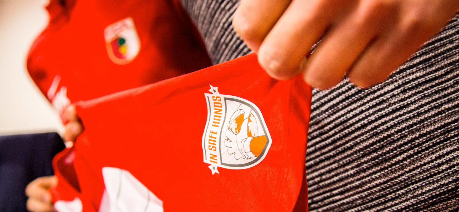 FC Augsburg spielt mit In safe hands e.V. Logo!